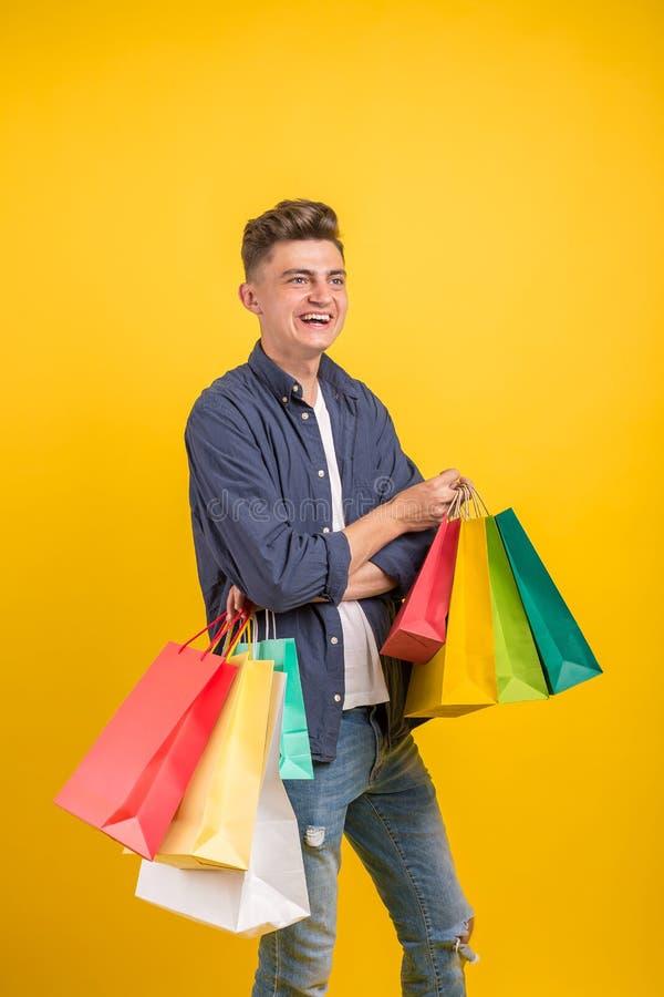 Εντυπωσιασμένος νεαρός άνδρας με τις ζωηρόχρωμες τσάντες αγορών στα χέρια με το ανοικτό στόμα, ευτυχές μετά από επιτυχές στοκ εικόνα με δικαίωμα ελεύθερης χρήσης