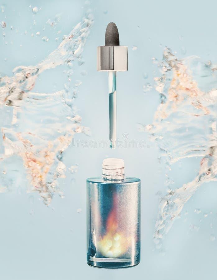 Ενυδατώνοντας του προσώπου μπουκάλι ορών ή πετρελαίου με τον παφλασμό σιφωνίων και νερού στο μπλε υπόβαθρο στοκ φωτογραφίες