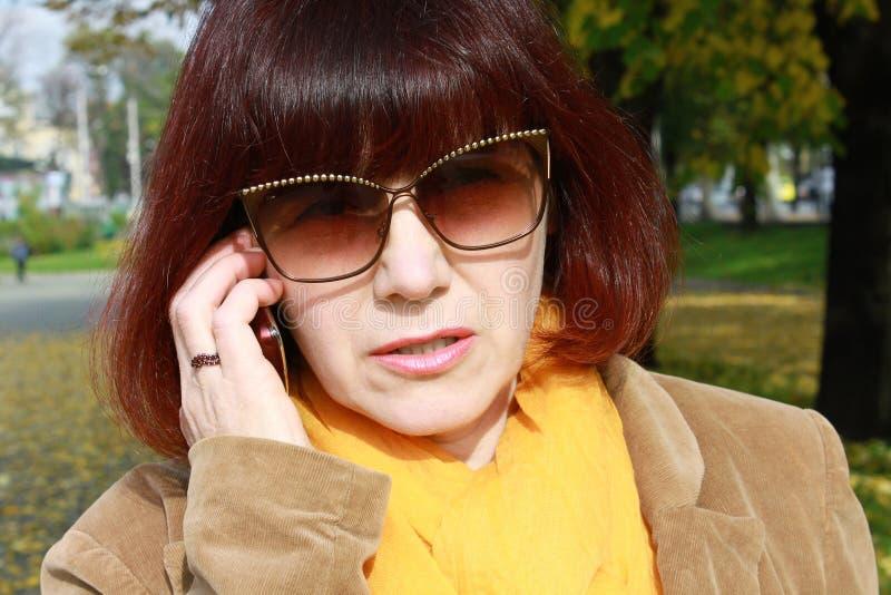 Ενδιαφερόμενη ώριμη γυναίκα στο τηλέφωνο στοκ εικόνες