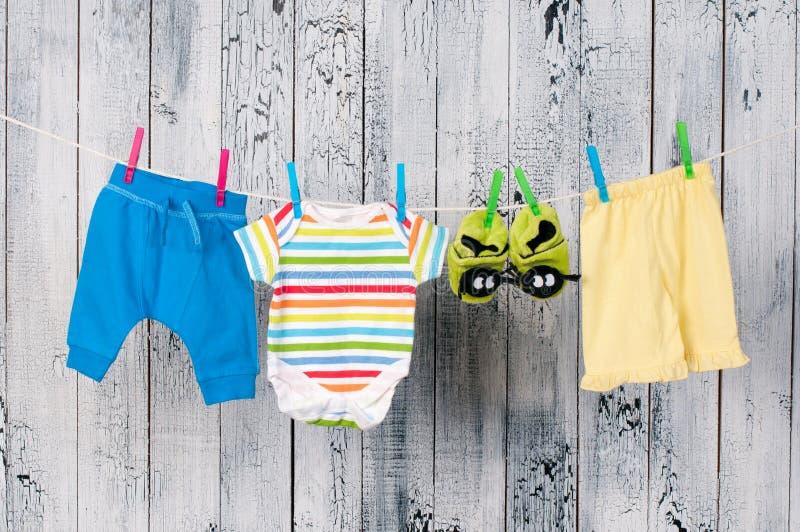 Ενδύματα μωρών που κρεμούν στη σκοινί για άπλωμα. στοκ εικόνα