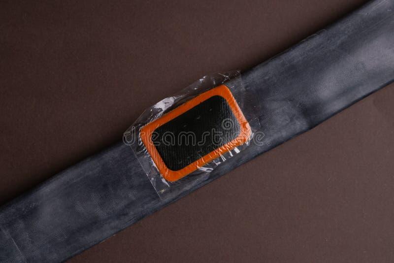 Εξάρτηση επισκευής ποδηλάτων, κάμερα ροδών στο ξύλινο υπόβαθρο Μπάλωμα στη κάμερα του ποδηλάτου στοκ εικόνα με δικαίωμα ελεύθερης χρήσης