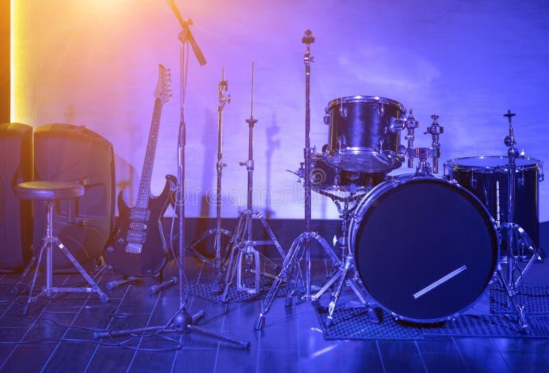 Εξάρτηση και κιθάρα τυμπάνων στην μπλε ελαφριά κινηματογράφηση σε πρώτο πλάνο στοκ φωτογραφίες με δικαίωμα ελεύθερης χρήσης