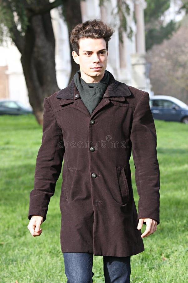 Εξάρτηση μόδας, όμορφος νεαρός άνδρας που περπατά - ελαφριά χρώματα στοκ φωτογραφία