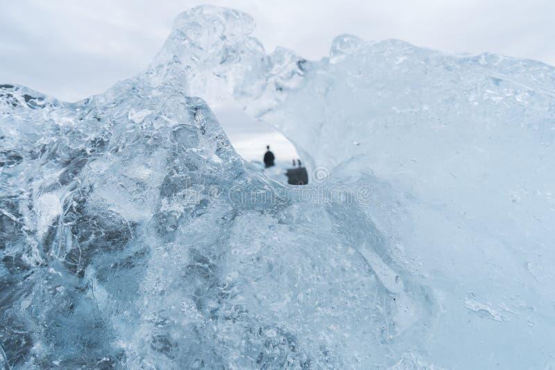 Εξέταση μέσω ενός παγόβουνου τους τουρίστες στην Ισλανδία στοκ εικόνες
