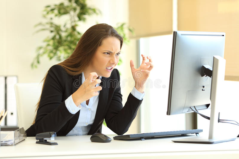 Εξαγριωμένη επιχειρηματίας που χρησιμοποιεί έναν υπολογιστή στοκ εικόνες