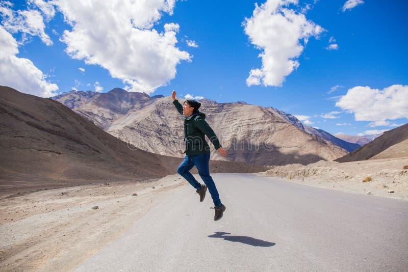 Εξαιρετικά ευτυχής νέος αρσενικός τουρίστας που πηδά στη εθνική οδό με τα γιγαντιαία βουνά πίσω στοκ φωτογραφία