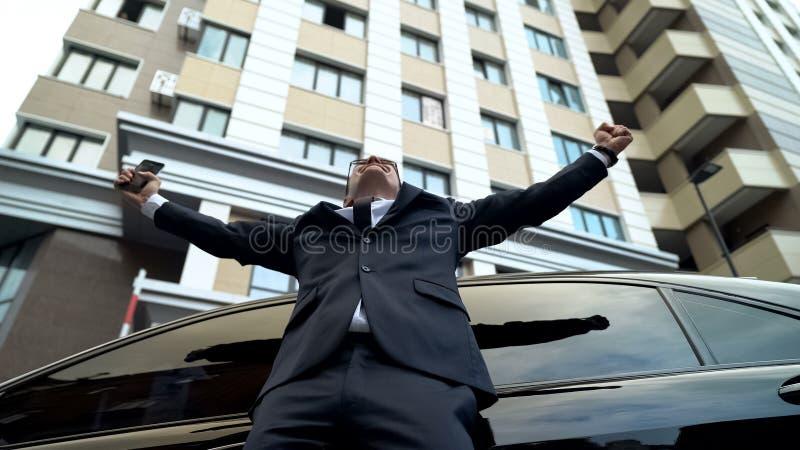 Εξαιρετικά ευτυχή όπλα διάδοσης επιχειρηματιών, νικητής λαχειοφόρων αγορών επίπεδου και αυτοκίνητο στοκ εικόνα με δικαίωμα ελεύθερης χρήσης