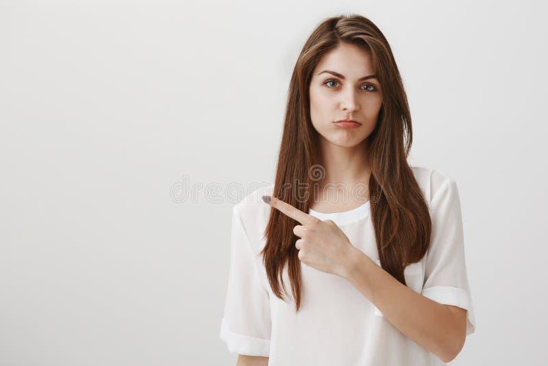 Εξαιρετικά ζηλότυπη ένδειξη φίλων στο πορτοφόλι θέλει όπως παρούσα Πορτρέτο της ελκυστικής υπόδειξης κοριτσιών brunette στοκ εικόνα με δικαίωμα ελεύθερης χρήσης
