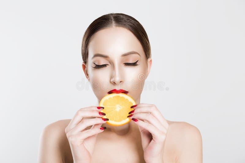 Εξαιρετικό φαγητό για έναν υγιεινό τρόπο ζωής Όμορφη νεαρή, χωρίς ρούχα γυναίκα που κρατά ένα κομμάτι πορτοκάλι στο στόμα της ενώ στοκ φωτογραφίες με δικαίωμα ελεύθερης χρήσης