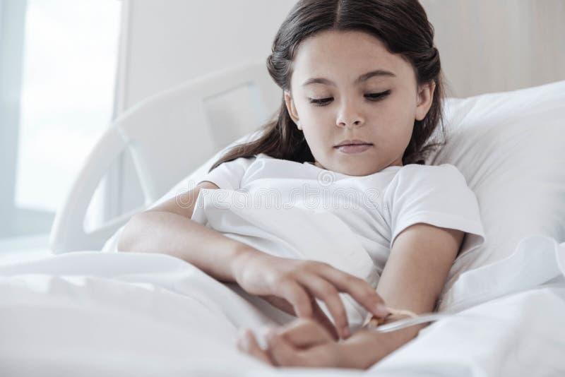 Εξαντλημένη νέα κυρία που εξετάζει τον εγχθμένο μετρητή πτώσης στο κρεβάτι στοκ φωτογραφία με δικαίωμα ελεύθερης χρήσης