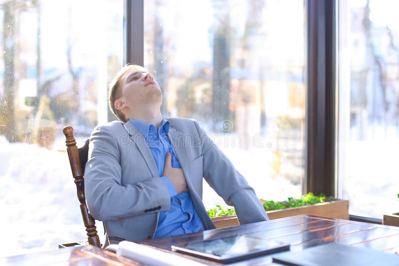 Εξαντλημένο άτομο που στηρίζεται στον καφέ και που χρησιμοποιεί το κοντινό έγγραφο α ρόλων ταμπλετών στοκ εικόνες με δικαίωμα ελεύθερης χρήσης