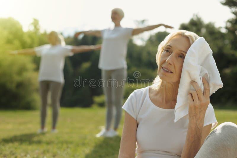 Εξαντλημένο σκουπίζοντας μέτωπο γυναικών μετά από το workout υπαίθρια στοκ εικόνα με δικαίωμα ελεύθερης χρήσης