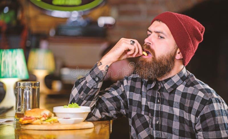 Εξαπατήστε το γεύμα Υψηλά τρόφιμα θερμίδας Εύγευστη burger έννοια Απολαύστε το γούστο φρέσκο burger Το πεινασμένο άτομο Hipster τ στοκ φωτογραφία με δικαίωμα ελεύθερης χρήσης