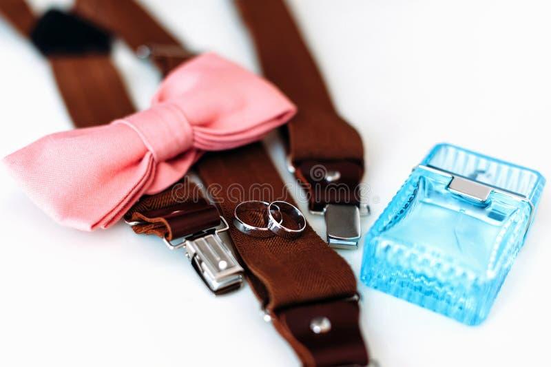 Εξαρτήματα ατόμων Γαμήλια δαχτυλίδια, δεσμός τόξων, parfume, suspenders στοκ εικόνες με δικαίωμα ελεύθερης χρήσης