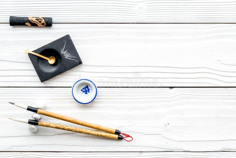 Εξαρτήματα για την κινεζική ή ιαπωνική καλλιγραφία Ειδική μάνδρα γραψίματος, μελάνι στο άσπρο ξύλινο διάστημα άποψης υποβάθρου το στοκ εικόνες