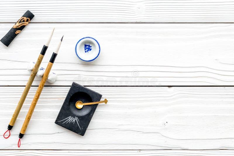 Εξαρτήματα για την κινεζική ή ιαπωνική καλλιγραφία Ειδική μάνδρα γραψίματος, μελάνι στο άσπρο ξύλινο αντίγραφο άποψης υποβάθρου τ στοκ εικόνα