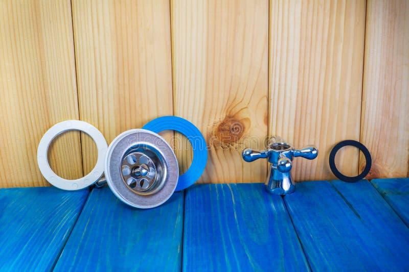 Εξαρτήματα για τις επισκευές ή την πλύση υδραυλικών στην κουζίνα σε ένα ξύλινο υπόβαθρο στοκ φωτογραφία