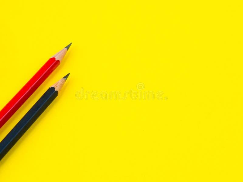 Εξαρτήματα γραφείων, κόκκινα και μαύρα μολύβια στο κίτρινο υπόβαθρο στοκ εικόνες