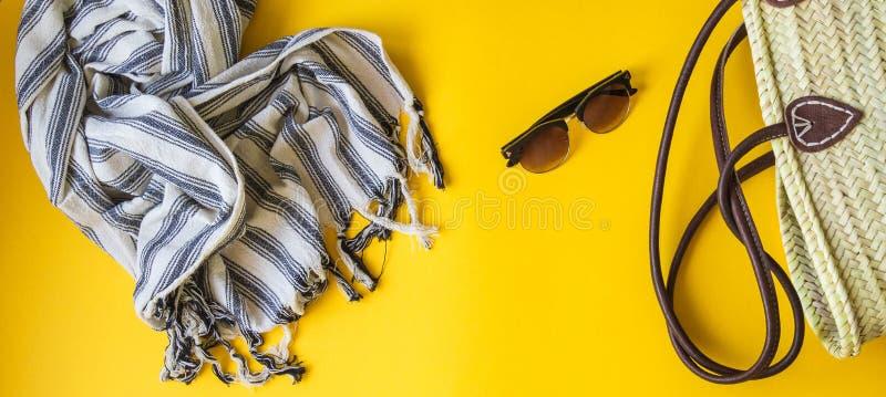 Εξαρτήματα γυναικών για παραθαλάσσιες διακοπές σε ένα κίτρινο υπόβαθρο Το ψάθινο επίπεδο τσαντών, πετσετών, παπουτσιών και γυαλιώ στοκ εικόνες