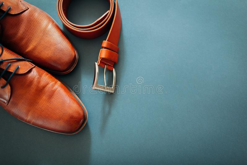 Εξαρτήματα επιχειρηματία Καφετιά παπούτσια δέρματος, ζώνη, άρωμα, χρυσά δαχτυλίδια E o στοκ φωτογραφίες