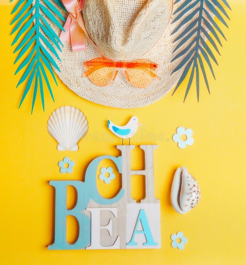 Εξαρτήματα θερινών παραλιών Καπέλο αχύρου με τα γυαλιά ηλίου, τα κοχύλια θάλασσας και τα τροπικά φύλλα στο κίτρινο υπόβαθρο, τοπ  στοκ φωτογραφία