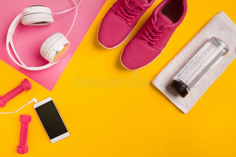 Εξαρτήματα ικανότητας σε ένα κίτρινο υπόβαθρο Πάνινα παπούτσια, μπουκάλι νερό, ακουστικά και αλτήρες στοκ εικόνες