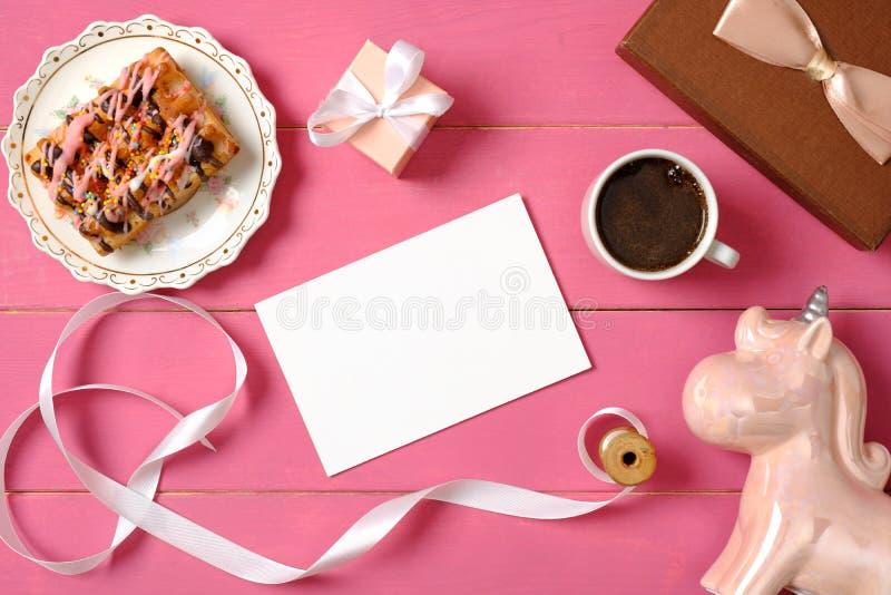 Εξαρτήματα κοριτσιών Hipster στο ρόδινο ξύλινο γραφείο: κενή κάρτα εγγράφου, κορδέλλα, μονόκερος, φλιτζάνι του καφέ, κιβώτιο δώρω στοκ εικόνα με δικαίωμα ελεύθερης χρήσης