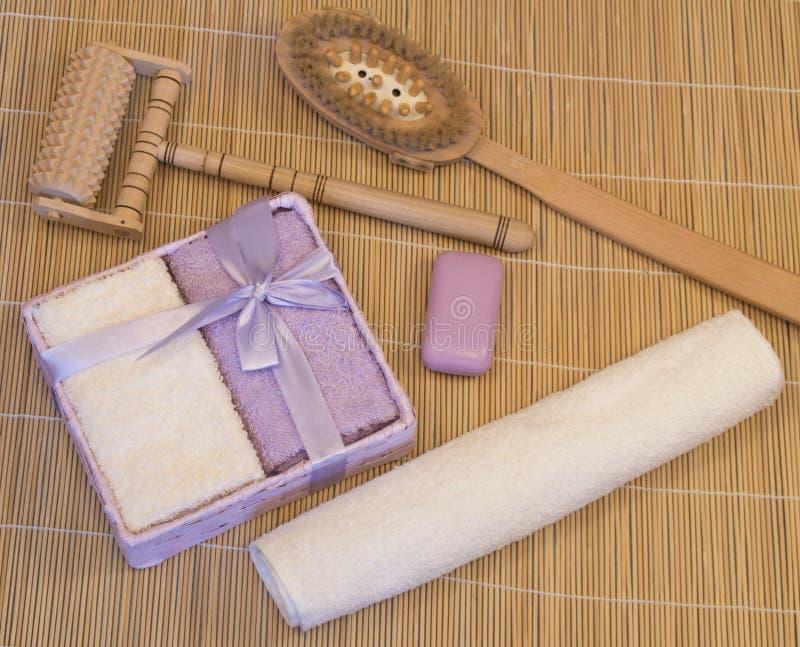 Εξαρτήματα λουτρών, ιώδης, μπεζ πετσέτα στο χαλί μπαμπού στοκ φωτογραφία με δικαίωμα ελεύθερης χρήσης