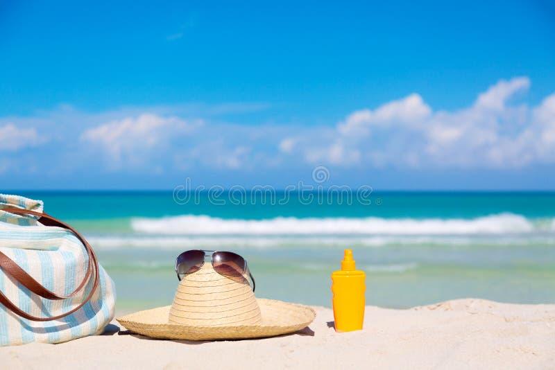 Εξαρτήματα παραλιών στην άμμο για την έννοια θερινών διακοπών Τσάντα, καπέλο αχύρου με τα γυαλιά ηλίου και sunscreen μπουκάλι λοσ στοκ φωτογραφία