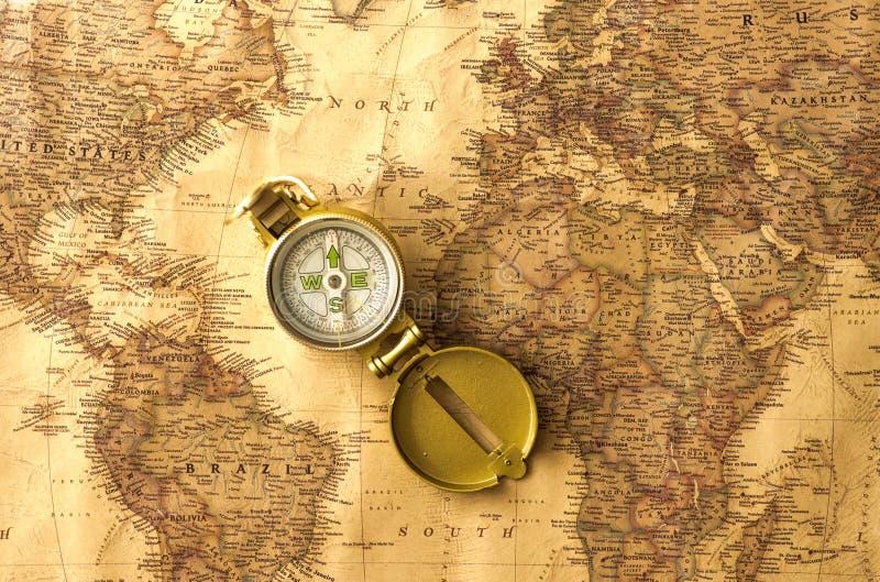 Εξαρτήματα ταξιδιού - πυξίδα στον παλαιό, παλαιό παγκόσμιο χάρτη στοκ φωτογραφίες με δικαίωμα ελεύθερης χρήσης