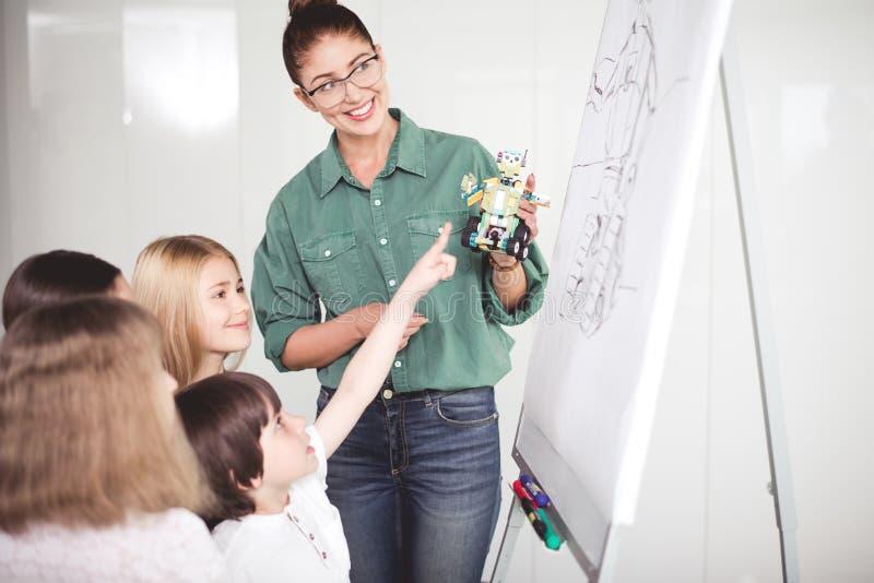 Εξερχόμενη γυναίκα και ικανοποιημένα παιδιά κατά τη διάρκεια του μαθήματος στοκ εικόνα