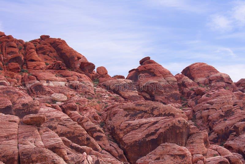 Εξετάζοντας ανοδικός έναν απότομο βράχο των οδοντωτών, απόκρημνων βράχων με έναν μπλε, νεφελώδη ουρανό στο υπόβαθρο Κόκκινος βράχ στοκ εικόνα