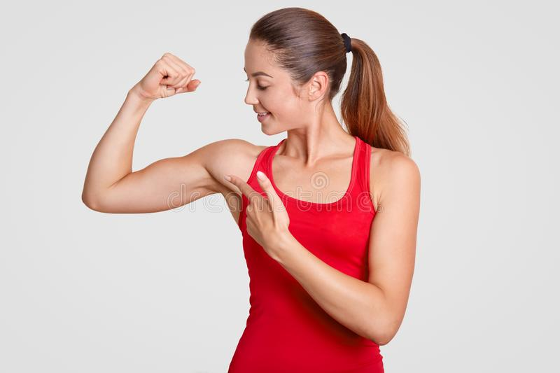 Εξετάστε τους δικέφαλους μυς μου! Η ισχυρή νέα χαριτωμένη γυναίκα πηγαίνει μέσα για τον αθλητισμό, έχει το ισχυρό σώμα, παρουσιάζ στοκ φωτογραφίες