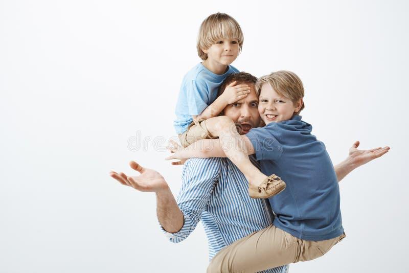 Εξετασμένος ευρωπαϊκός πατέρας που αυξάνει τους φοίνικες στην ανίδεη χειρονομία, που κολλά έξω τη γλώσσα και που εξετάζει τη κάμε στοκ εικόνες