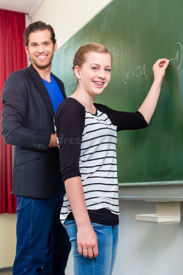 Εξεταστικός σπουδαστής δασκάλων κατά τη διάρκεια των μαθημάτων math στο σχολείο στοκ φωτογραφίες