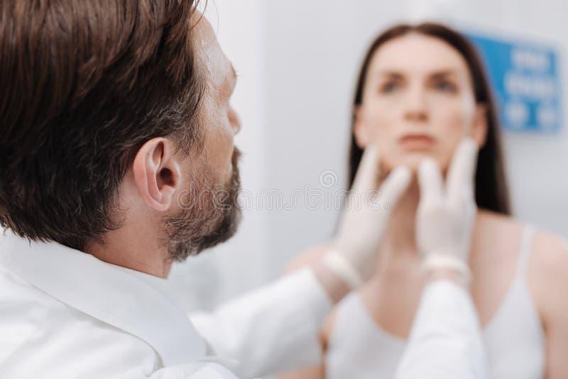 Εξευγενίστε τον πλαστικό χειρούργο που εξετάζει το πρόσωπο ασθενών στοκ εικόνες
