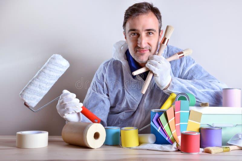 Εξοπλισμένος εργαζόμενος που παρουσιάζει τα προϊόντα χρωμάτων στον ξύλινο πίνακα στοκ φωτογραφία με δικαίωμα ελεύθερης χρήσης