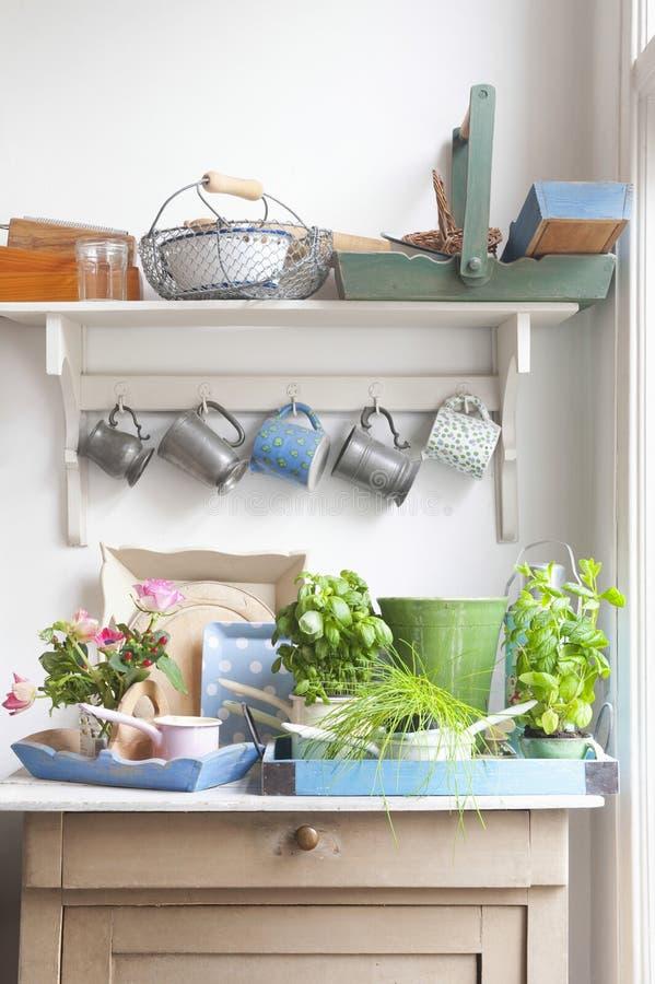 Εξοπλισμός κηπουρικής στο κομμό με τα φλυτζάνια που κρεμούν στην κουζίνα στοκ φωτογραφία