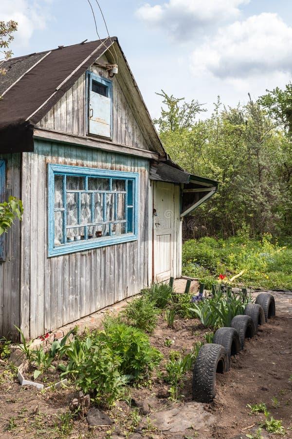 Εξοχικό σπίτι με το καλλιεργημένο έδαφος που περιβάλλεται από την πρασινάδα την άνοιξη στη Ρωσία Ρωσικό dacha στοκ εικόνες