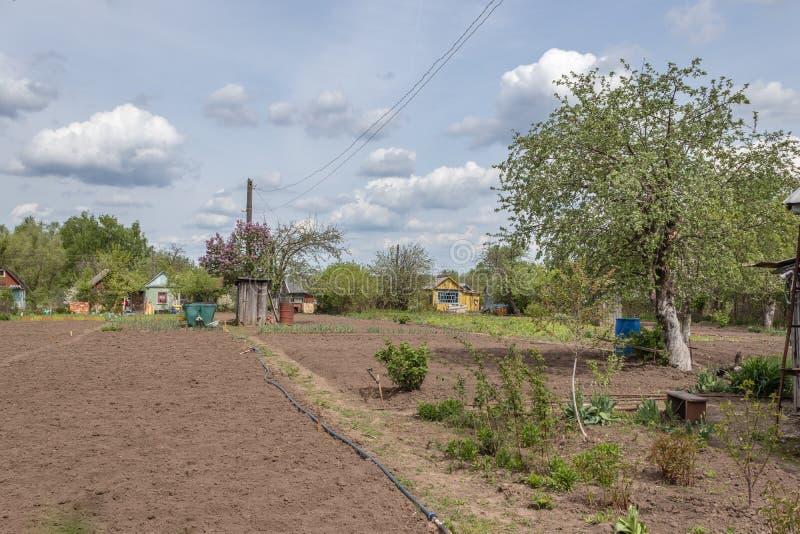 Εξοχικό σπίτι με το καλλιεργημένο έδαφος που περιβάλλεται από την πρασινάδα την άνοιξη στη Ρωσία Ρωσικό dacha στοκ εικόνες με δικαίωμα ελεύθερης χρήσης