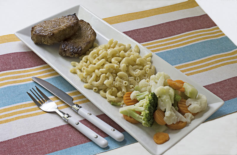 Εξυπηρέτηση γεύματος που αποτελείται από την μπριζόλα και τα μακαρόνια και veggies σε ένα στενόμακρο άσπρο πιάτο στοκ φωτογραφίες