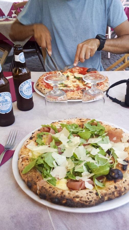 Εξυπηρέτηση ενός ποτηριού της ιταλικής μπύρας και μιας πίτσας στοκ εικόνες