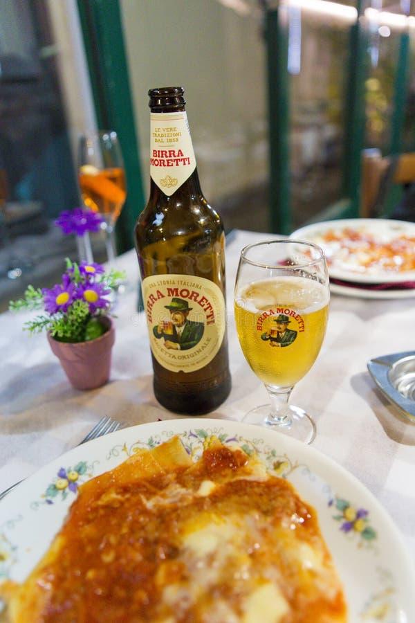 Εξυπηρέτηση ενός ποτηριού της ιταλικής μπύρας και ενός lasagna στοκ εικόνα με δικαίωμα ελεύθερης χρήσης