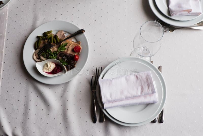 Εξυπηρετημένος για τον πίνακα εστιατορίων συμποσίου με τα πιάτα, πρόχειρο φαγητό, μαχαιροπήρουνα, γυαλιά νερού στοκ εικόνα