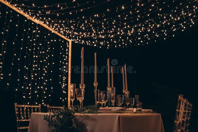 Εξυπηρετούμενος πίνακας γευμάτων με τα κεριά και τις γιρλάντες στοκ εικόνα με δικαίωμα ελεύθερης χρήσης