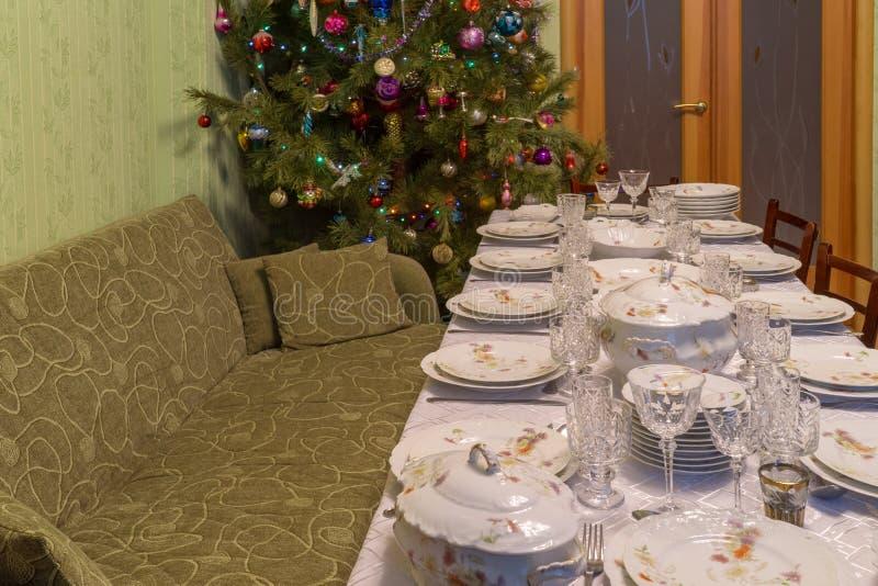Εξυπηρετούμενος πίνακας με το εορταστικό επιτραπέζιο σκεύος κοντά σε όμορφο διακοσμημένο Chr στοκ εικόνα