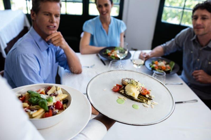 Εξυπηρετώντας γεύμα σερβιτόρων στην ομάδα φίλων στοκ φωτογραφία