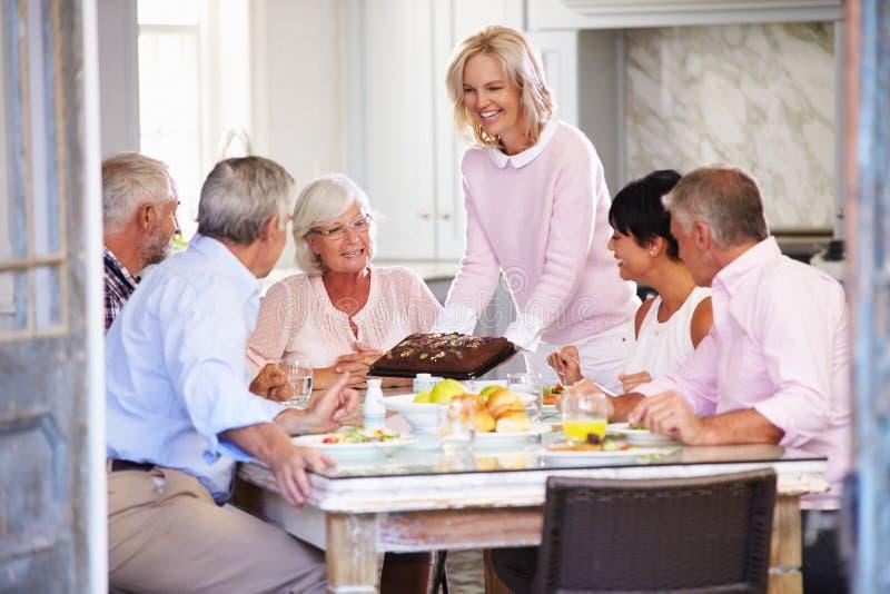 Εξυπηρετώντας κέικ γυναικών στην ομάδα φίλων που απολαμβάνουν το γεύμα στο σπίτι στοκ εικόνα