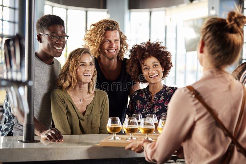Εξυπηρετώντας ομάδα σερβιτορών δοκιμής μπύρας φίλων στο φραγμό στοκ φωτογραφίες