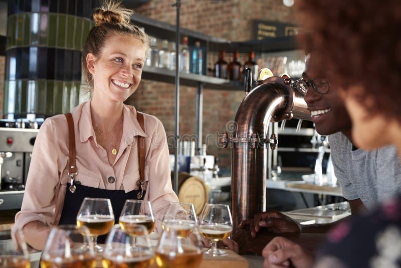 Εξυπηρετώντας ομάδα σερβιτορών δοκιμής μπύρας φίλων στο φραγμό στοκ εικόνα με δικαίωμα ελεύθερης χρήσης